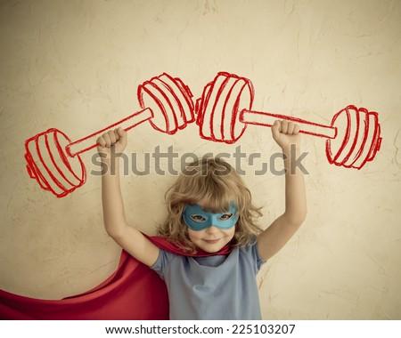 Superhero kid having fun at home. Retro toned