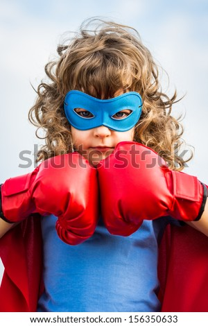 Superhero kid wearing boxing gloves against blue sky background Girl power and feminism concept