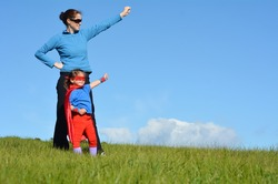 Superhero mother show her daughter how to be  a superhero against blue sky background with copy space. concept photo of Super hero, girl power, play pretend, childhood, imagination. Real people