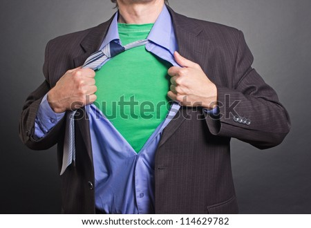 Superhero, young businessman tearing his shirt