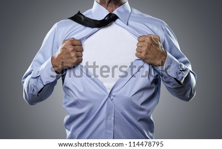 Superhero, young businessman tearing his shirt off isolated on gray background with copy space