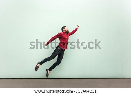Superman style. Enthusiasm concept. Young adult bearded businessman felt himself a superhero. Outdoor, gray wall #715404211