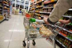 Supermarket Aisle View of a Shopping Trolley and Shelves - Image has a Shallow Depth of Field