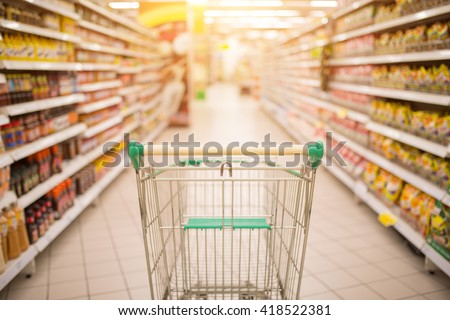 Supermarket aisle with empty red shopping cart with customer defocus background