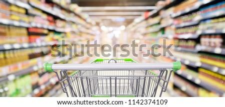 supermarket shelves aisle with empty shopping cart defocused interior blur bokeh light background