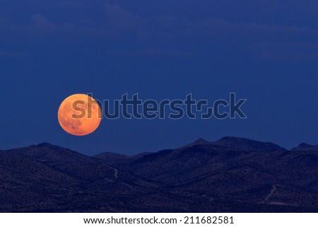 Supermoon rising over desert mountains in Barstow, California.