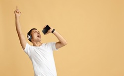 Superstar and imaginary microphone at free time during covid. Millennial guy student in white t-shirt and headphones sings in smartphone as star, isolated on beige background, studio shot, copy space