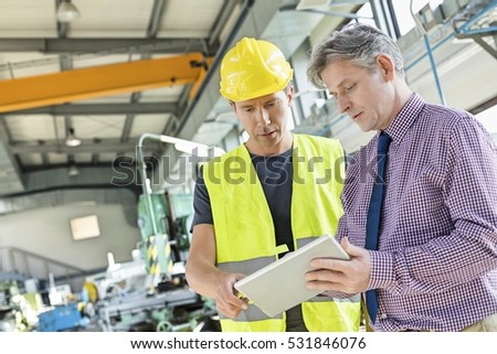Supervisor and manual worker using digital tablet in metal industry #531846076