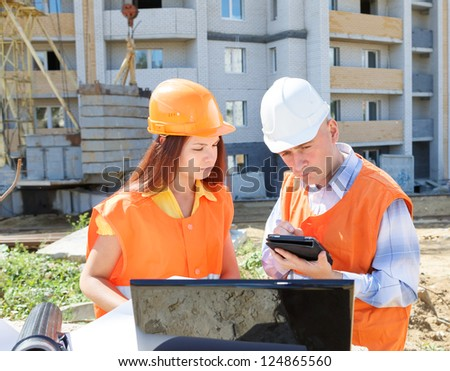 Supervisor and Subordinate employee looking at laptop Builders