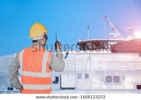 supervisor, foreman,  inspector, surveyor in dock yard with walkie talkie in hand wearing safety helmet building the ship under repairing in shipyard on navigation bridge deck background.