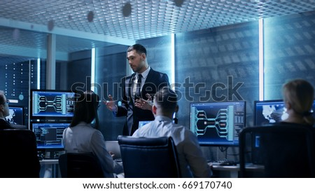 Supervisor Holds Briefing for His Employees in System Control Center Full of Monitors and Servers. Possibly Government Agency Conducts Investigation.  #669170740