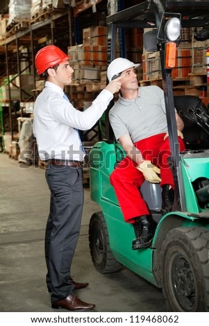 Supervisor instructing forklift driver at warehouse