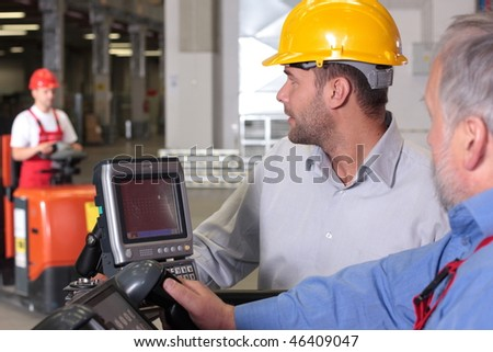 supervisor talking to forklift operator in warehouse #46409047