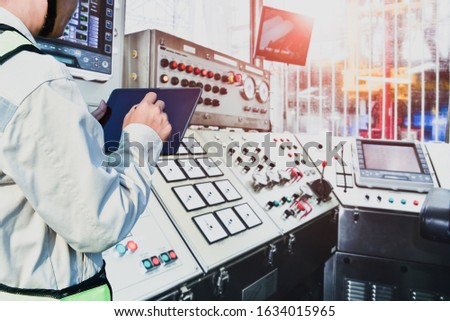 supervisor worker with tablet to operator recording operation of oil and gas process at oil rig plant, offshore rig in the sea, operator monitor production process, routine daily record controller. Foto stock ©
