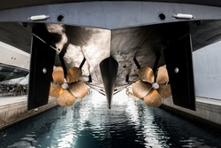 Superyacht being lowered into the water after winter haul out at shipyard, with freshly auti-fauled hull and polished propellers about to touch the water