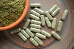 Supplement kratom green capsules and powder on brown plate. Herbal product alt-medicine kratom is  opioid. Home alternative pain remedy, opioid addiction, dangerous painkiller. Selective focus