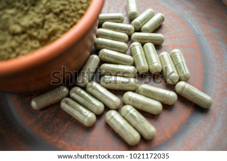 Supplement kratom green capsules and powder on brown plate. Herbal product alt-medicine kratom is  opioid. Home alternative pain remedy, opioid addiction, dangerous. Close up. Selective focus #1021172035