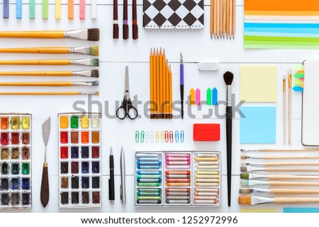 Supplies set on desk top view, creative tools for school creative work on white wooden table, background with drawing painting stationery, color paints brushes pencils crayons, copy space, flat lay