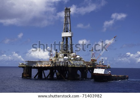 supply vessel along side drilling rig in offshore area during operation of supply