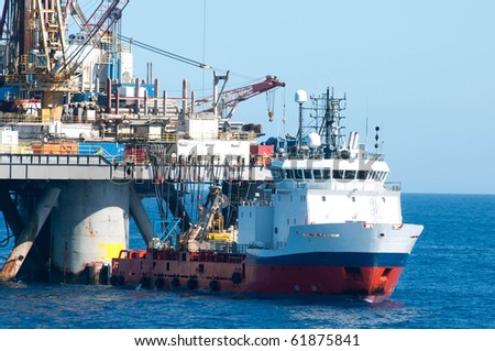 Supply vessel during operation along side with a drilling rig.  Coast of Brazil - stock photo