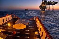 Supply vessel rolling in the sea during cargo operations for offshore oil production platform.