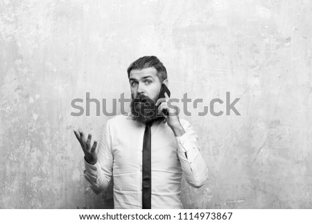 Support service. manager or bearded man with long beard and stylish hair on surprised face in tie and white shirt on beige background speaking on mobile phone, conversation and information #1114973867