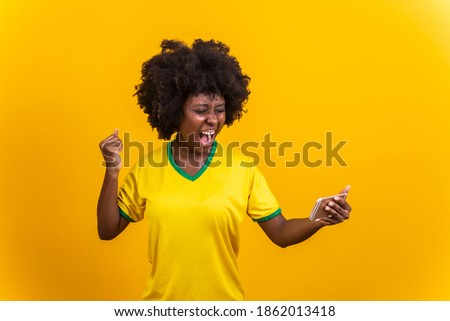 Supporter of the Brazilian football team celebrating a goal by watching the smartphone Foto stock ©