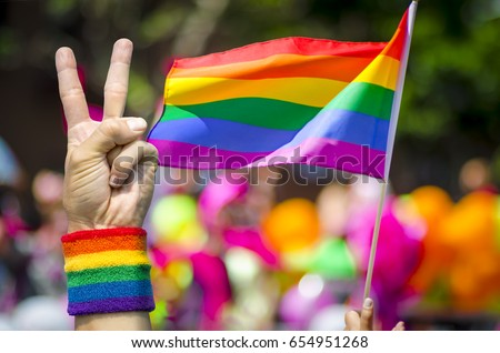 Supporting hand makes peace sign in front of a rainbow flag flying on the sidelines of a summer gay pride parade #654951268