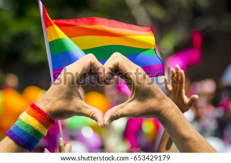 Supporting hands make heart sign and wave in front of a rainbow flag flying on the sidelines of a summer gay pride parade Stockfoto ©