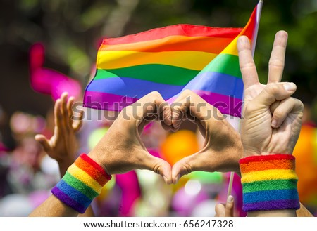 Supporting hands make peace and heart signs in front of a rainbow flag flying on the sidelines of a summer gay pride parade #656247328