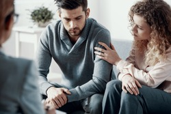 Supportive beautiful wife touching husband's arm during psychotherapy session for married couples with problems
