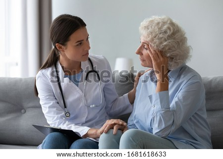Supportive female nurse visit old grandmother patient at home listen to complains concerns, attentive young woman doctor consulting mature senior grandma, elderly medical healthcare concept