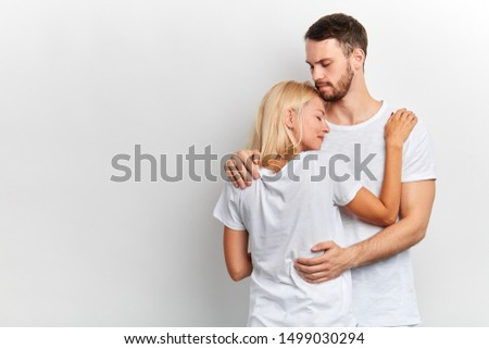Supportive guy hugs and tries to appease his girlfriend who has desperate look, girl has problems, isolated white background, studio shot, copy space. love, negative feeling and emotion,lifestyle