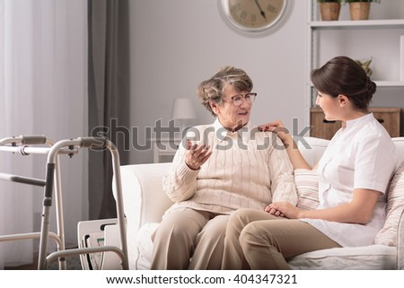 Supportive young carer sitting with older patient