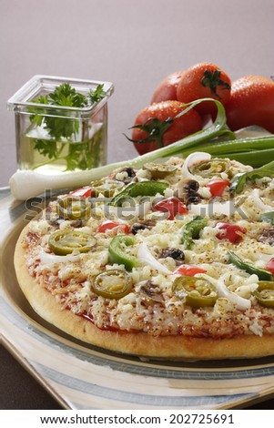 Supreme Pizza in a serving plate with vegetables around.