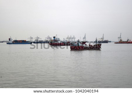 Surabaya, Indonesia - January 24, 2016: The busy Port of Tanjung Perak Surabaya on a cloudy day. It is the largest harbor in East Java, Indonesia #1042040194