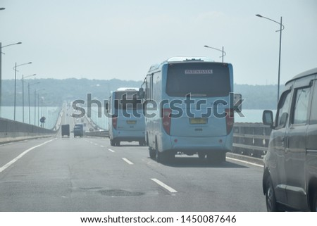 Surabaya, Indonesia - June27, 2019:  The bus drove on the Suramadu bridge highway from the direction of Surabaya to Kota Bangkalan, Madura, East Java, Indonesia #1450087646