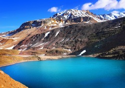 Suraj Tal (Surya taal) lake, Lahaul and Spiti valley, Himachal Pradesh, Northern India. Beautiful scenic view, high mountain range with melting snow and bright blue water. View from Leh - Manali road
