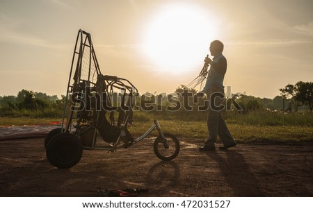 Suratthani,Thailand,August 21,2016 : Man with Paramotor flight training in the morning sky, beautiful natural countryside in surat thani province,Thailand  #472031527