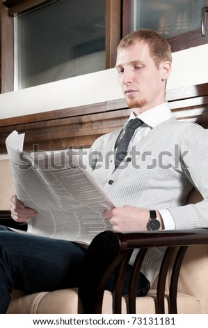 Sure young business man in office rest room  interior with fresh newspaper