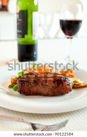 Surf and turf meal with fresh scampi and steak. Red wine in the background and shallow depth of field.