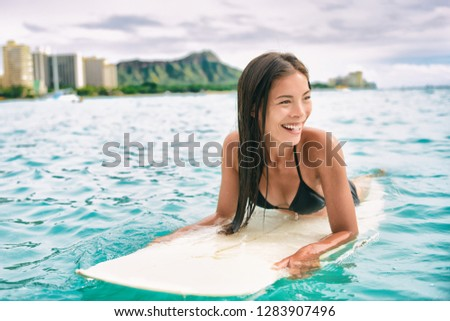 Surf class in Waikiki Hawaii - Surfing Asian surfer girl on surfbaord lesson in Hawaii paddling in ocean waves. Sexy sports athlete training in water. Watersport active lifestyle. #1283907496