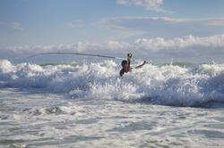 Surf fisherman in the waves. Surf fishing scene