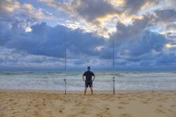 Surf fisherman waiting for fish on a beach of Atlantic ocean. Adventure fishing, wild fishing
