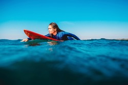Surf girl floats on surfboard. Woman in ocean during surfing. Surfer and ocean
