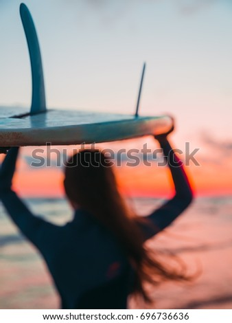 Stock Photo Surf girl go to surfing. Woman with surfboard on a beach at sunset or sunrise. Surfer and ocean