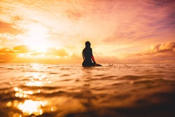 Surf girl in ocean at sunset or sunrise. Winter surfing in ocean