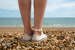 Surf girl on shingle beach with shell anklet