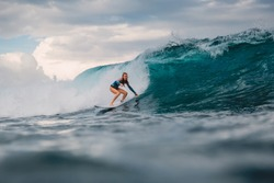 Surf girl on surfboard. Surfer woman and big blue wave