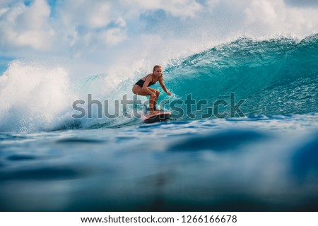 Surf girl on surfboard. Surfer woman and blue wave #1266166678